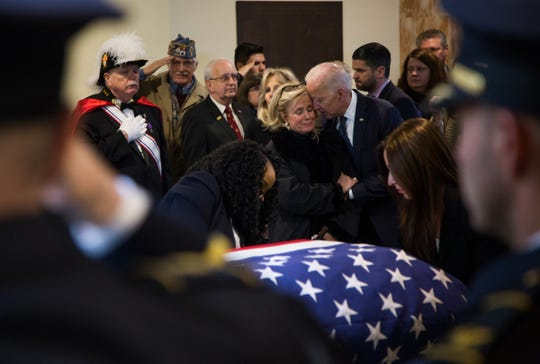 Rep. Debbie Dingell is embraced by former Vice President Joe Biden as a flag is fastened to the casket of her late husband former U.S. Representative John Dingell at the end of his funeral at Church of the Divine Child in Dearborn on Tuesday, February 12, 2019.