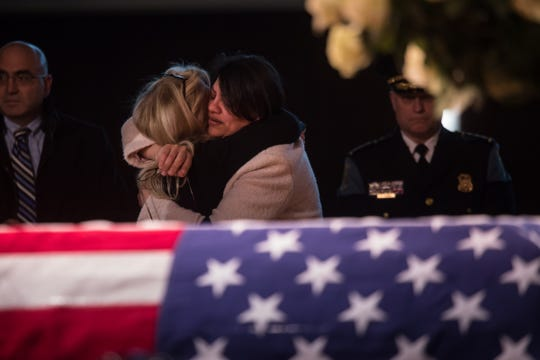 U.S. Rep.Rashida Tlaib embraces Rep. Debbie Dingell by the casket of her late husband former US Representative John D. Dingell during his visitation at the Ford Community and Performing Arts Center in Dearborn on Monday, February 11, 2019.