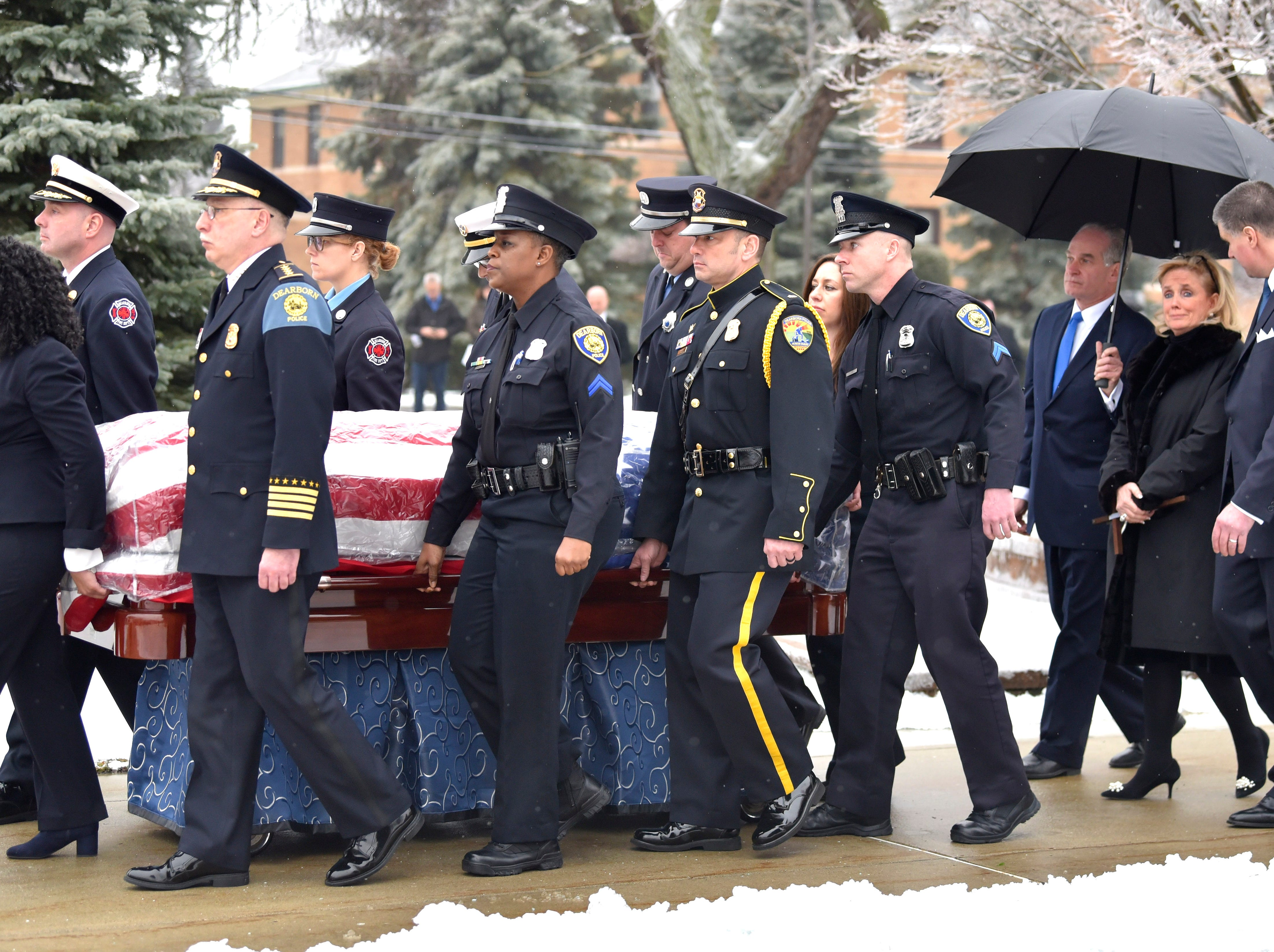 U.S. Congresswoman Debbie Dingell, center-rear, follows the casket of her husband, John Dingell Jr., as Dearborn police officers and fire fighters carry it to the hearse.