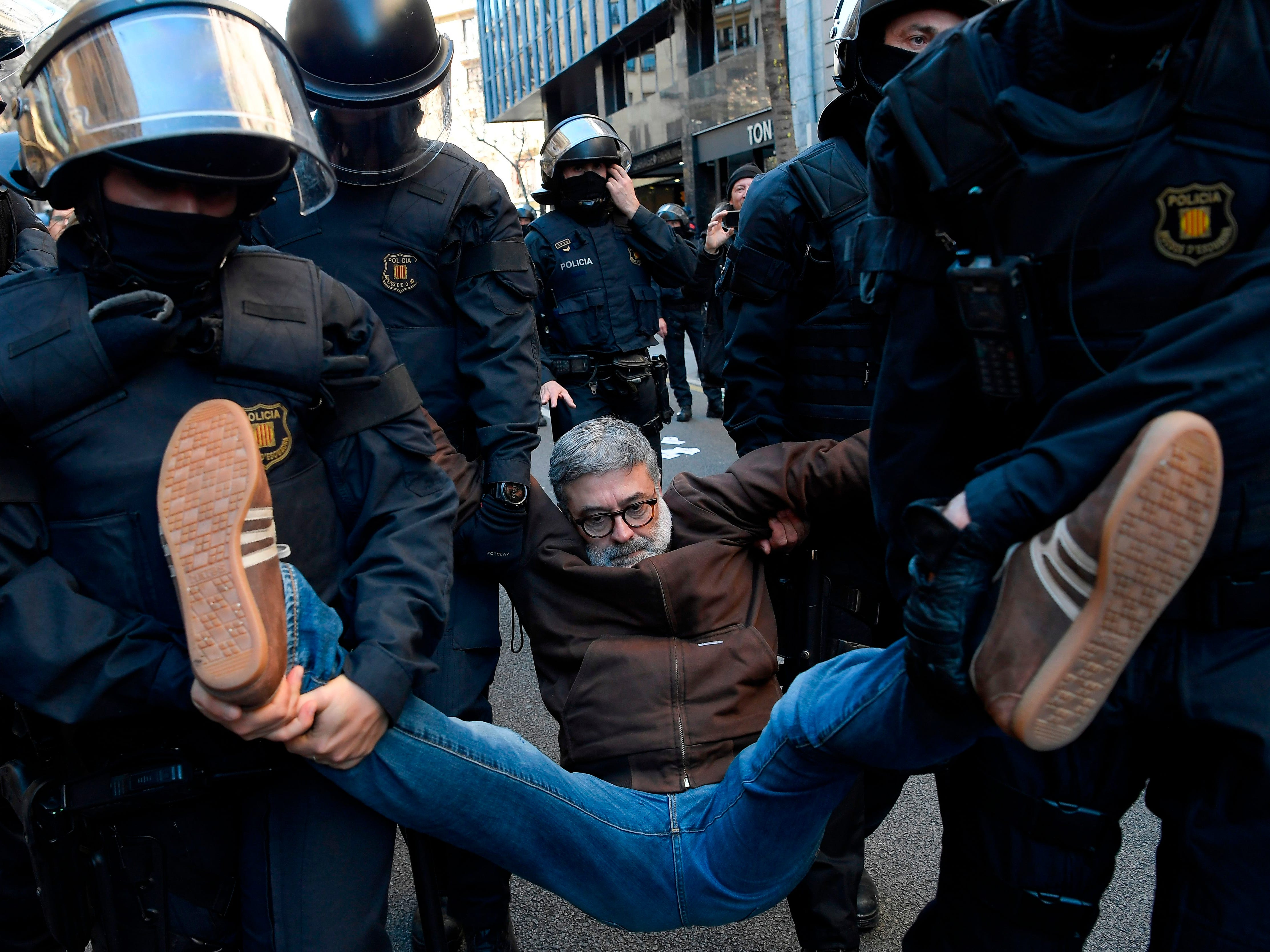 Catalan regional police forces Mossos d'Esquadra carry Catalan regional MP Carles Riera of the Candidatura d'Unitat Popular - CUP (Popular Unity Candidacy) after he joined demonstrators blocking a street in Barcelona to protest against the trial of former Catalan separatist leaders on Feb. 12, 2019. Twelve former Catalan leaders go on trial at Spain's Supreme Court for their role in a failed 2017 bid to break away from Spain.