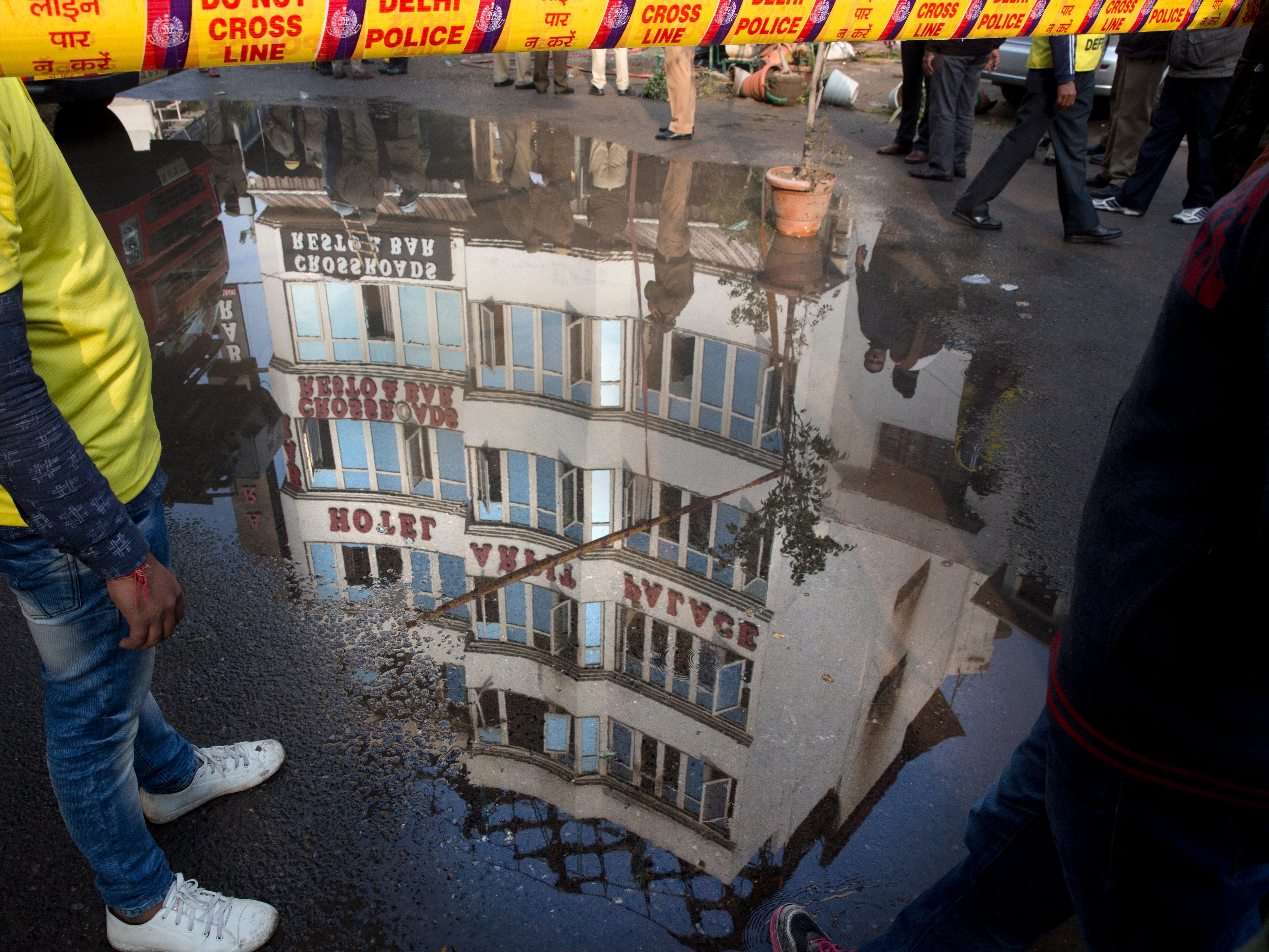 The Arpit Palace Hotel is reflected in a puddle after an early morning fire there killed more than a dozen people in the Karol Bagh neighborhood of New Delhi, India, Tuesday, Feb. 12, 2019.