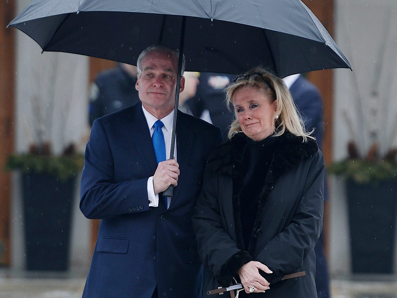 Funeral Director Alan Laumer of Verheyden Funeral Home holds a umbrella for Debbie Dingell as she watches her husband John D. Dingell's casket loaded into the hearse after the funeral.