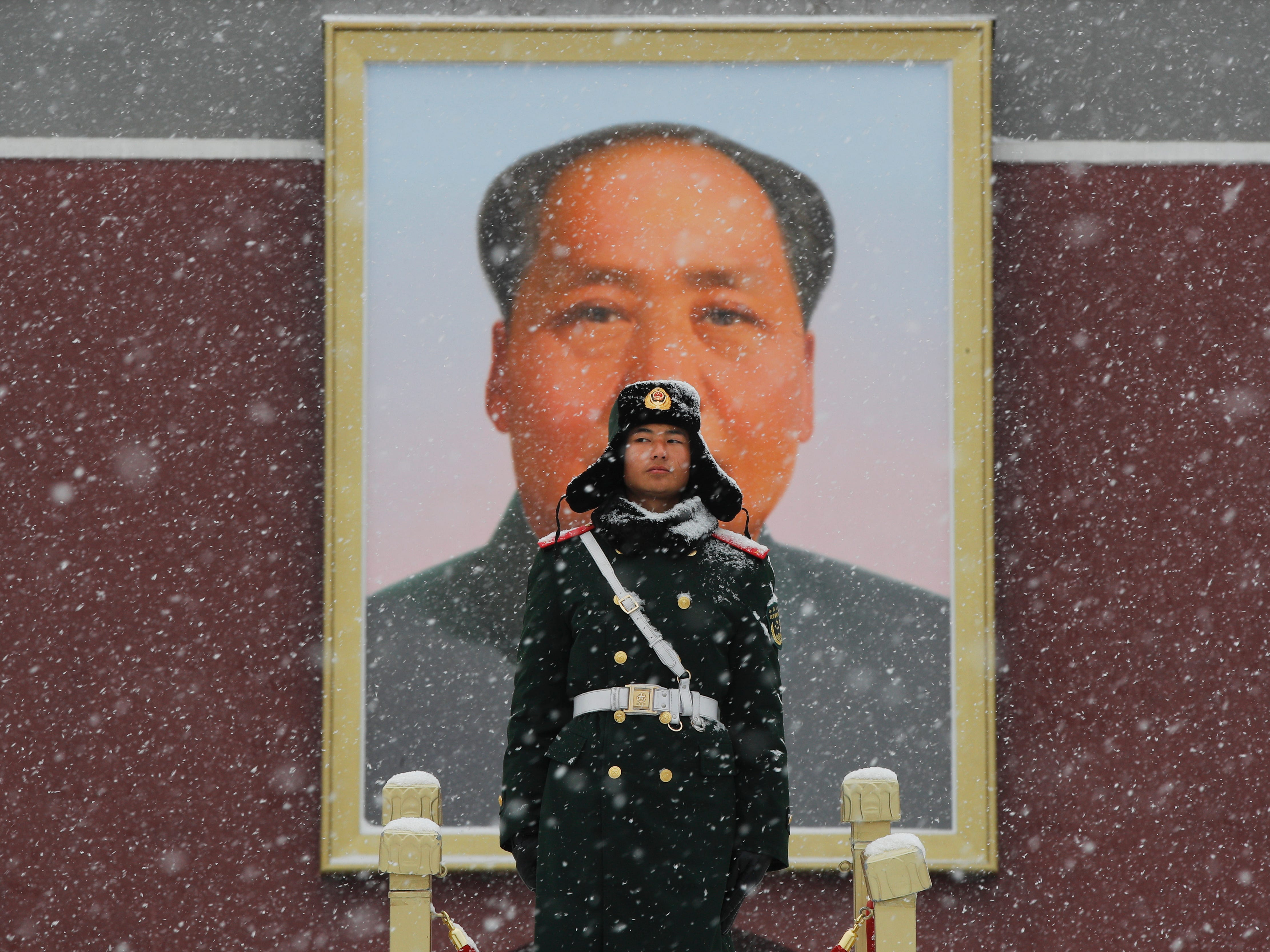A Chinese paramilitary police officer stands guard under the portrait of former leader Mao Zedong outside the Tiananmen Gate as snow falls in Beijing, Tuesday, Feb. 12, 2019. China's capital is mostly dry in the winter but a storm system brought snow to the city on Tuesday morning.