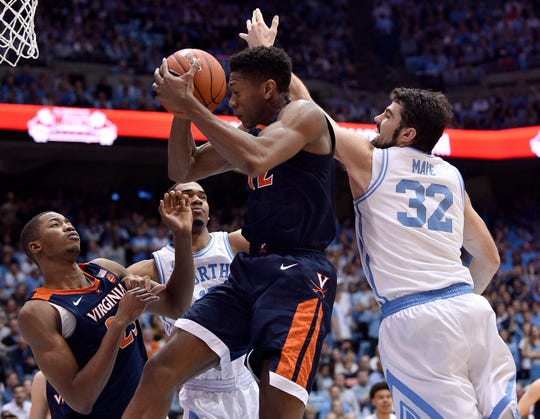 De'Andre Hunter (12) of the Virginia Cavaliers battles Luke Maye (32) of the North Carolina Tar Heels for a rebound during the second half Monday.  Virginia won 69-61.