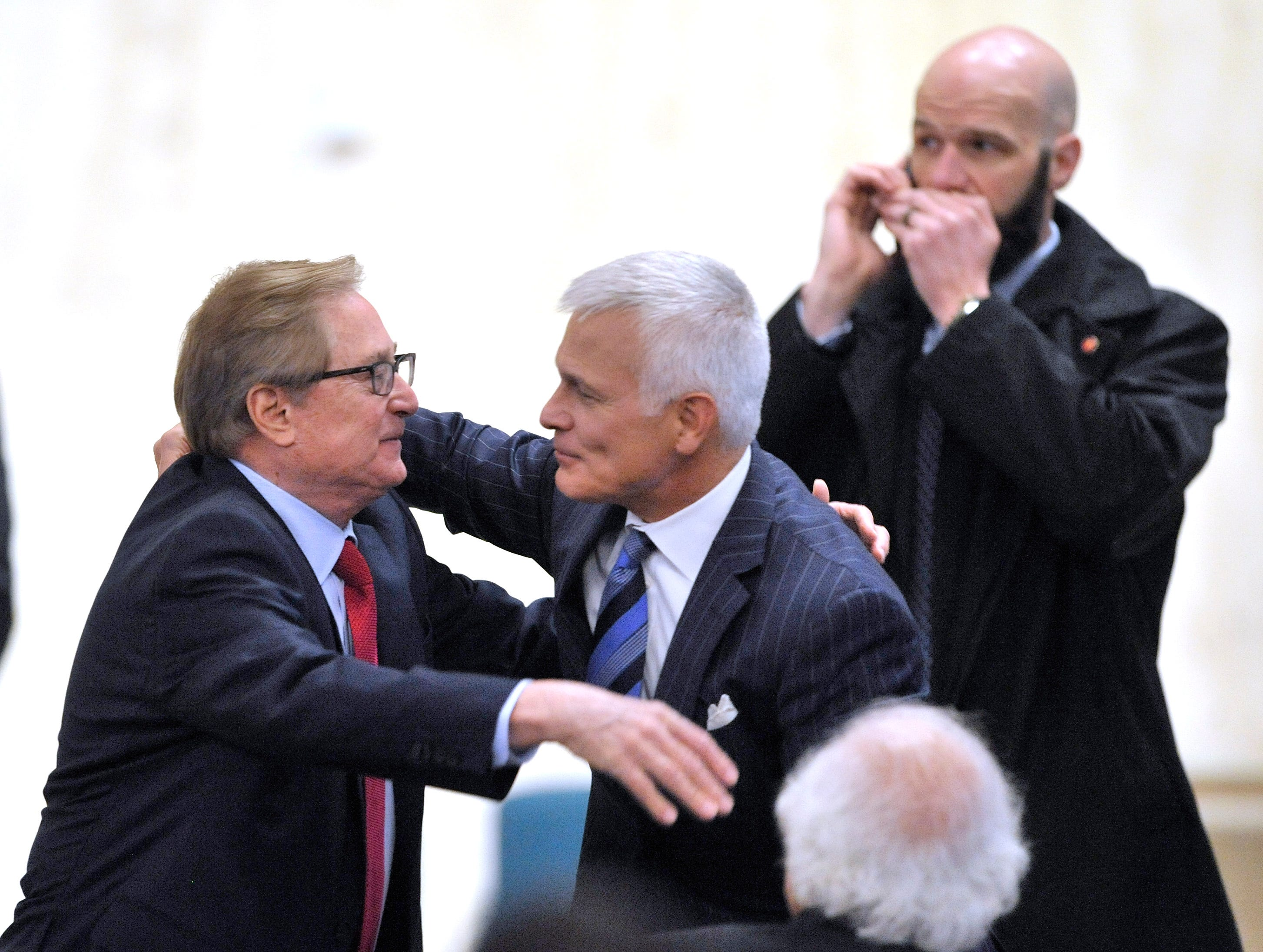 Former Michigan Governor Jim Blanchard, left, receives a hug before the funeral mass.