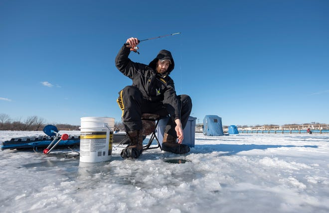 Matt Grassa, of St. Clair Shores, enjoys a day of ice fishing on Lake St. Clair near the Clinton River Cut-Off Boat Launch in Harrison Twp., January 21, 2019.