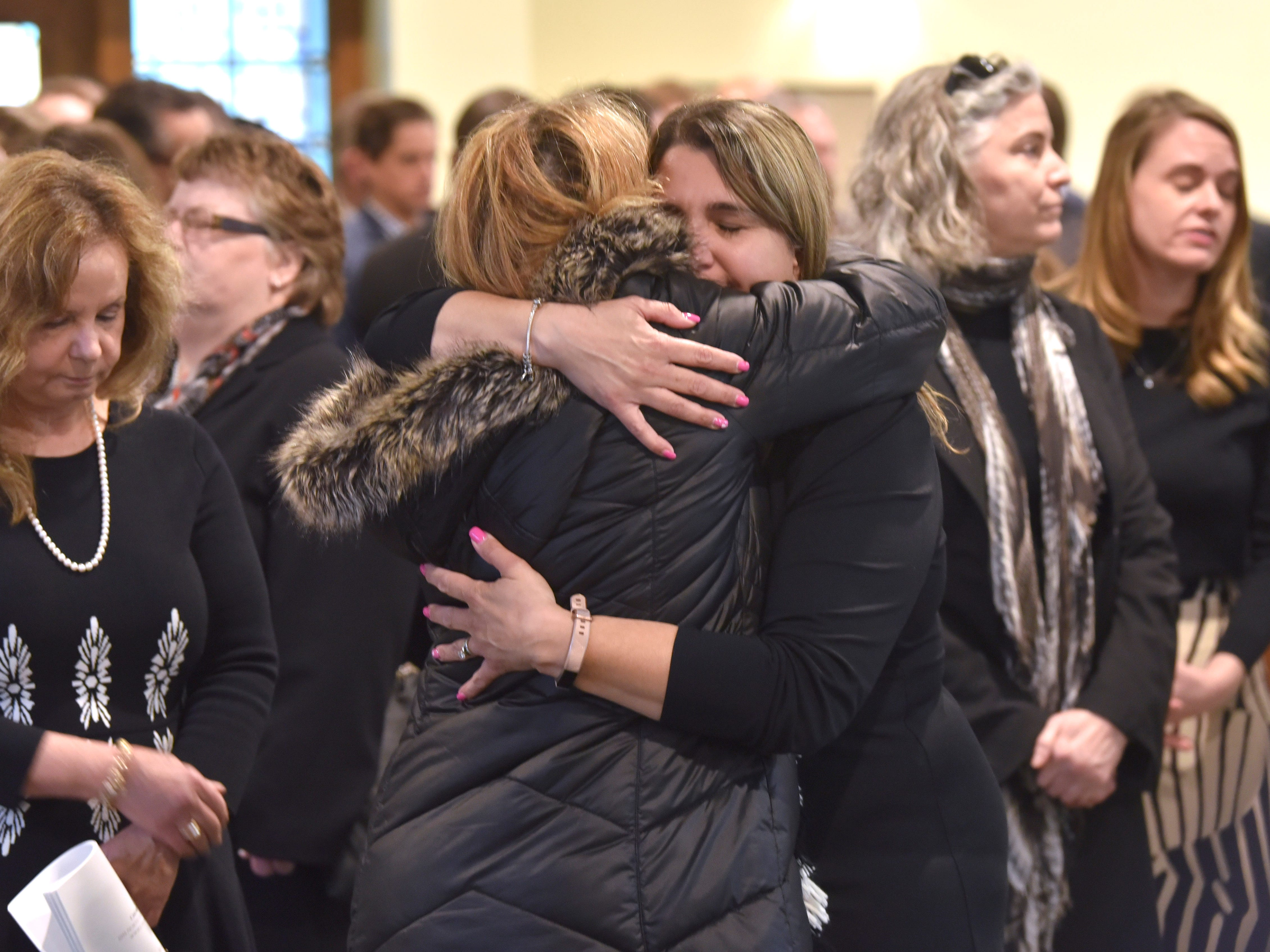 Former Dingell Congressional aide and page Rafeef Samo, center-right, hugs family friend Siham Awada-Jaafar (center-left) as Samo stands with other honorary pallbearers, who are all former Dingell staffers.