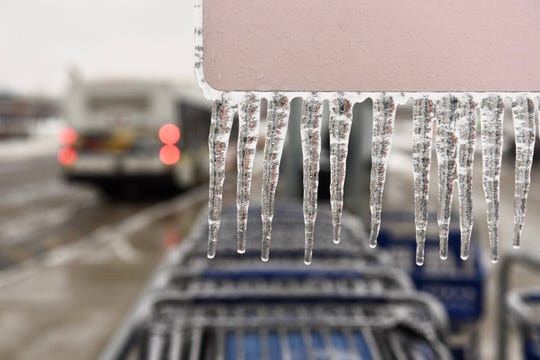 Icicles hang on a shopping cart return sign at the Meijer superstore along 8 Mile Road in Detroit on Tuesday, February 12, 2019.
