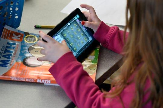 A kindergarten student plays an educational game on a data pad in Farmington Hills.