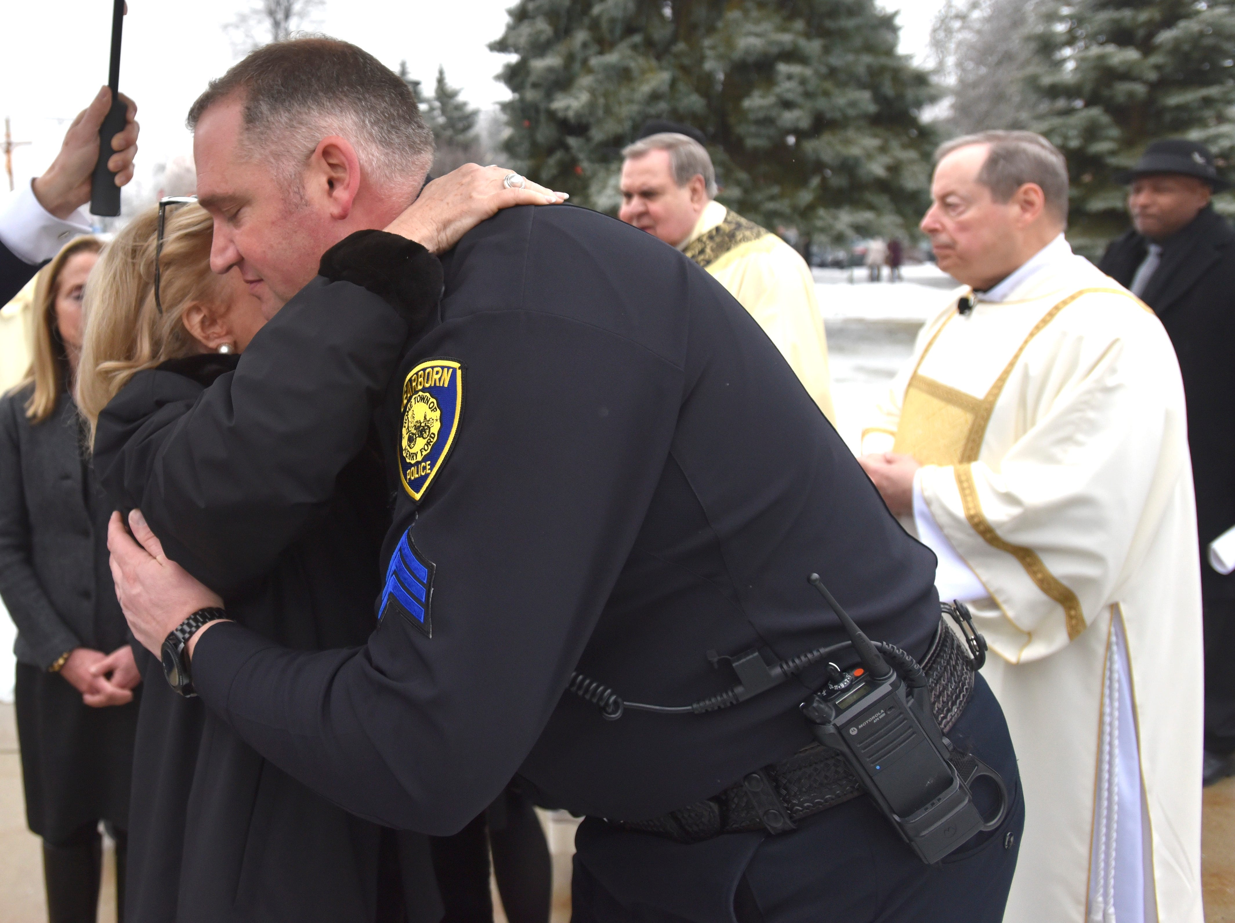 Dearborn Police Sgt. Jason Skoczylas hugs U.S. Rep. Debbie Dingell before the hearse leaves.