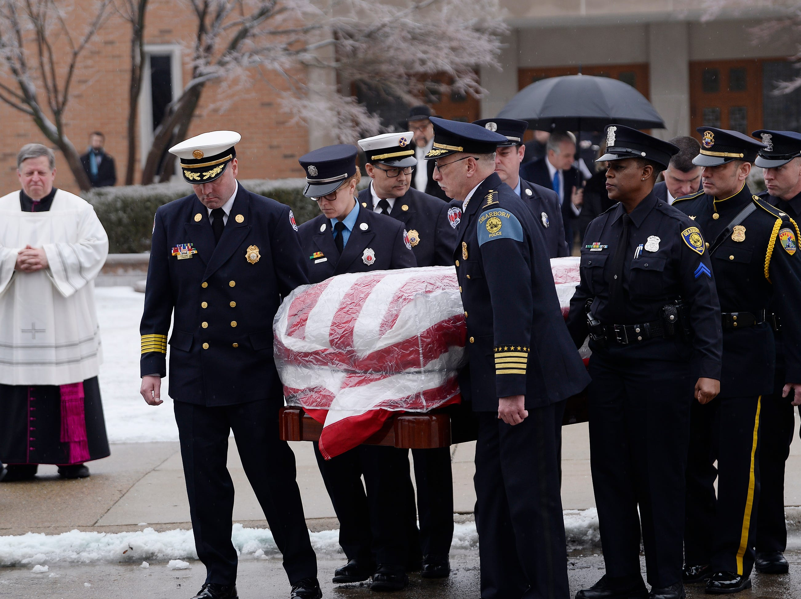 Dearborn Fire Chief Joseph Murray (left) and Dearborn Police Chief Ronald Haddad (center) along with other first responders carry the casket of former U.S. Rep. John D. Dingell to the hearse after the funeral.