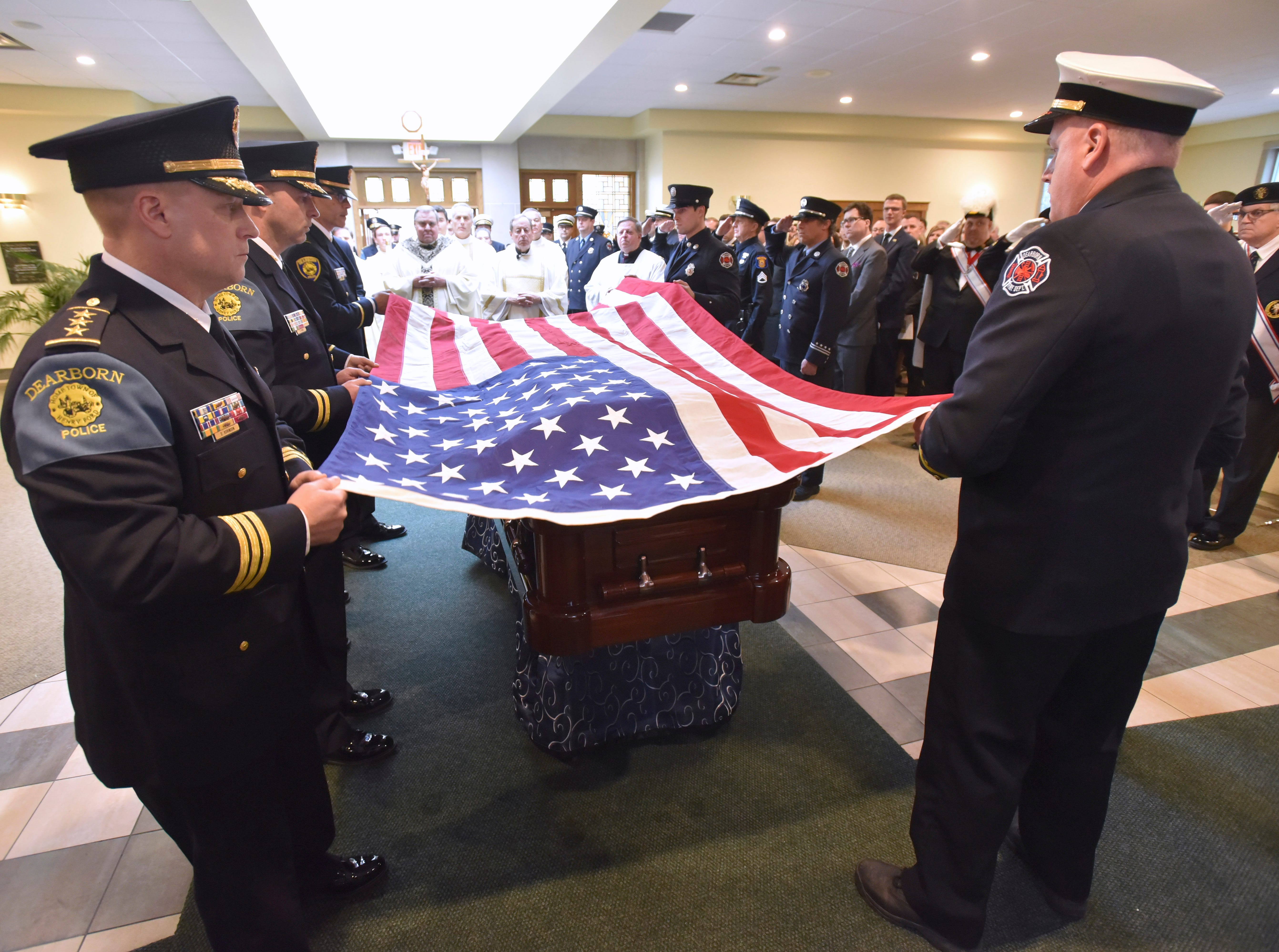 Dearborn police officers and fire fighters drape the American Flag over John Dingell Jr.'s casket at the end of the funeral service.