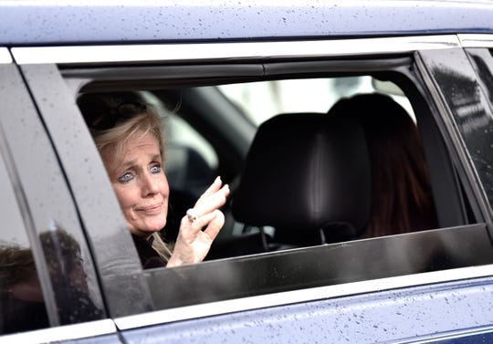 Debbie Dingell, U.S. Congresswoman and widow of the late John Dingell, Jr., waves before leaving the funeral.