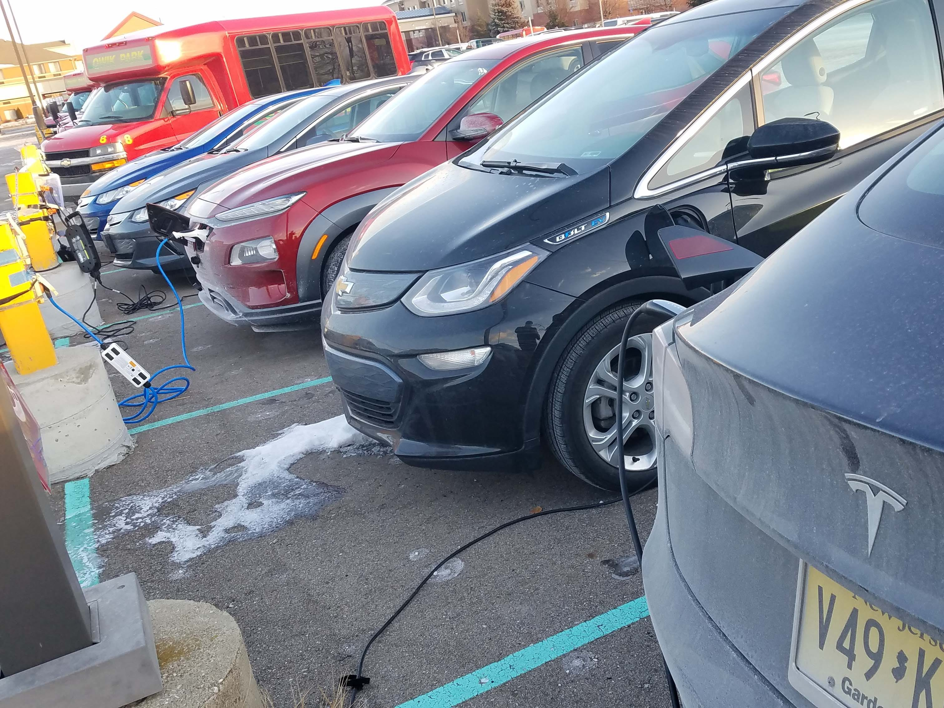 Charging stations are hard to come by in Metro Detroit. The 2019 Hyundai Kona EV (third from right) feeds at the electron teat with other battery-powered cars at QuickPark parking lot near Metro Airport.