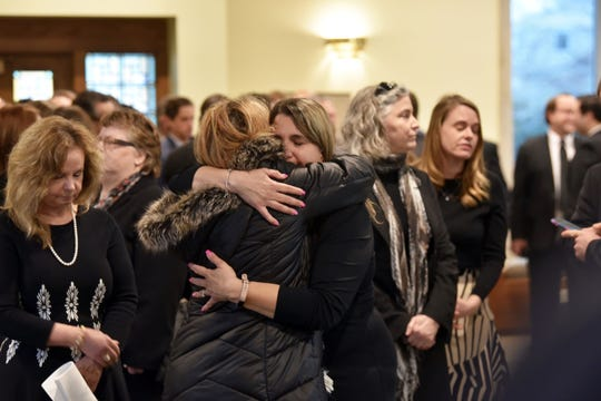 Former John Dingell Congressional aide and page Rafeef Samo, center-right, hugs family friend Siham Awada-Jaafar as Samo stands with other honorary pallbearers, who are all former Dingell staffers.