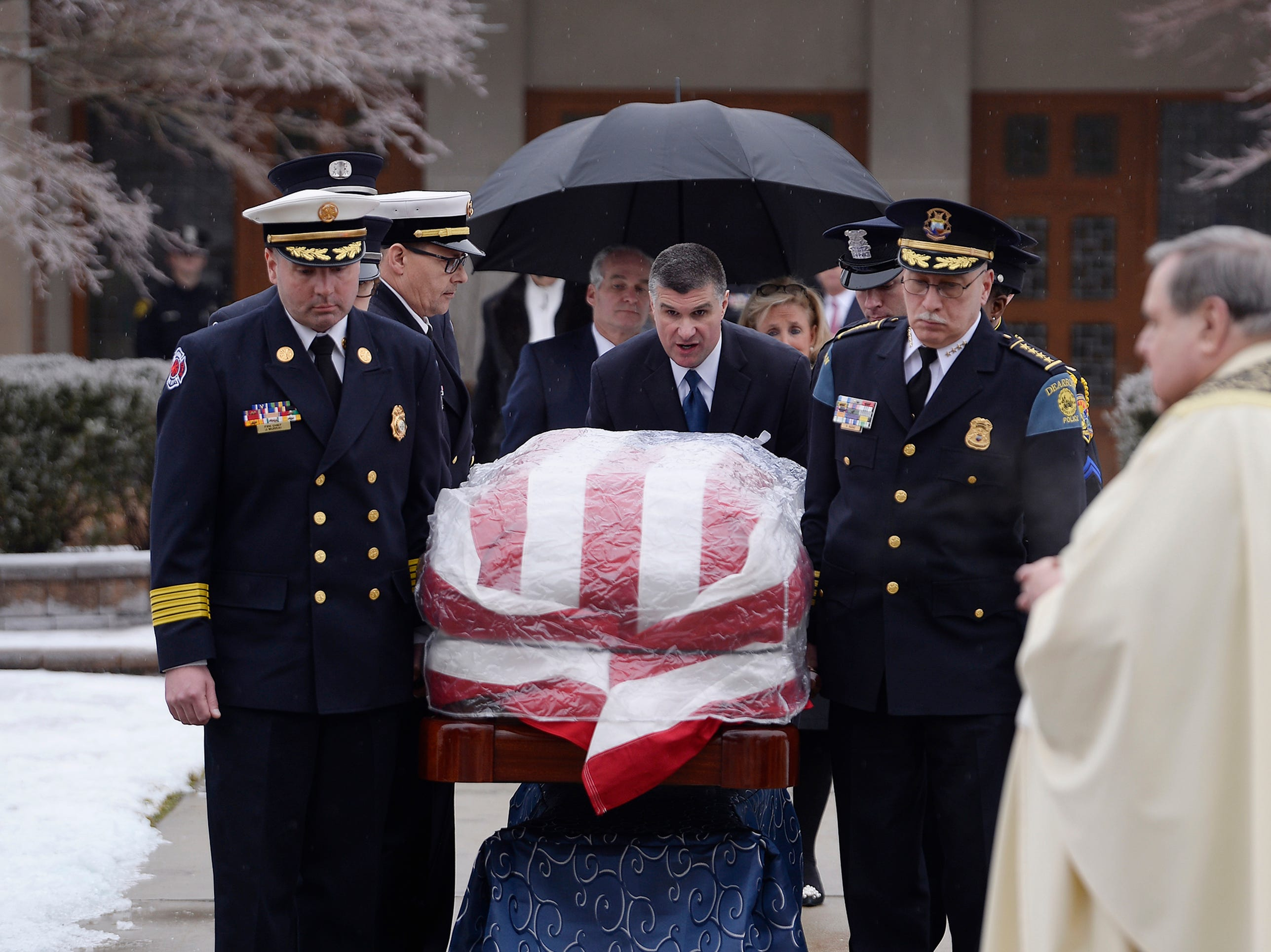 Dearborn Fire Chief Joseph Murray (left) and Dearborn Police Chief Ronald Haddad (right) along with other first responders carry the casket of former U.S. Rep. John D. Dingell to the hearse after the funeral.