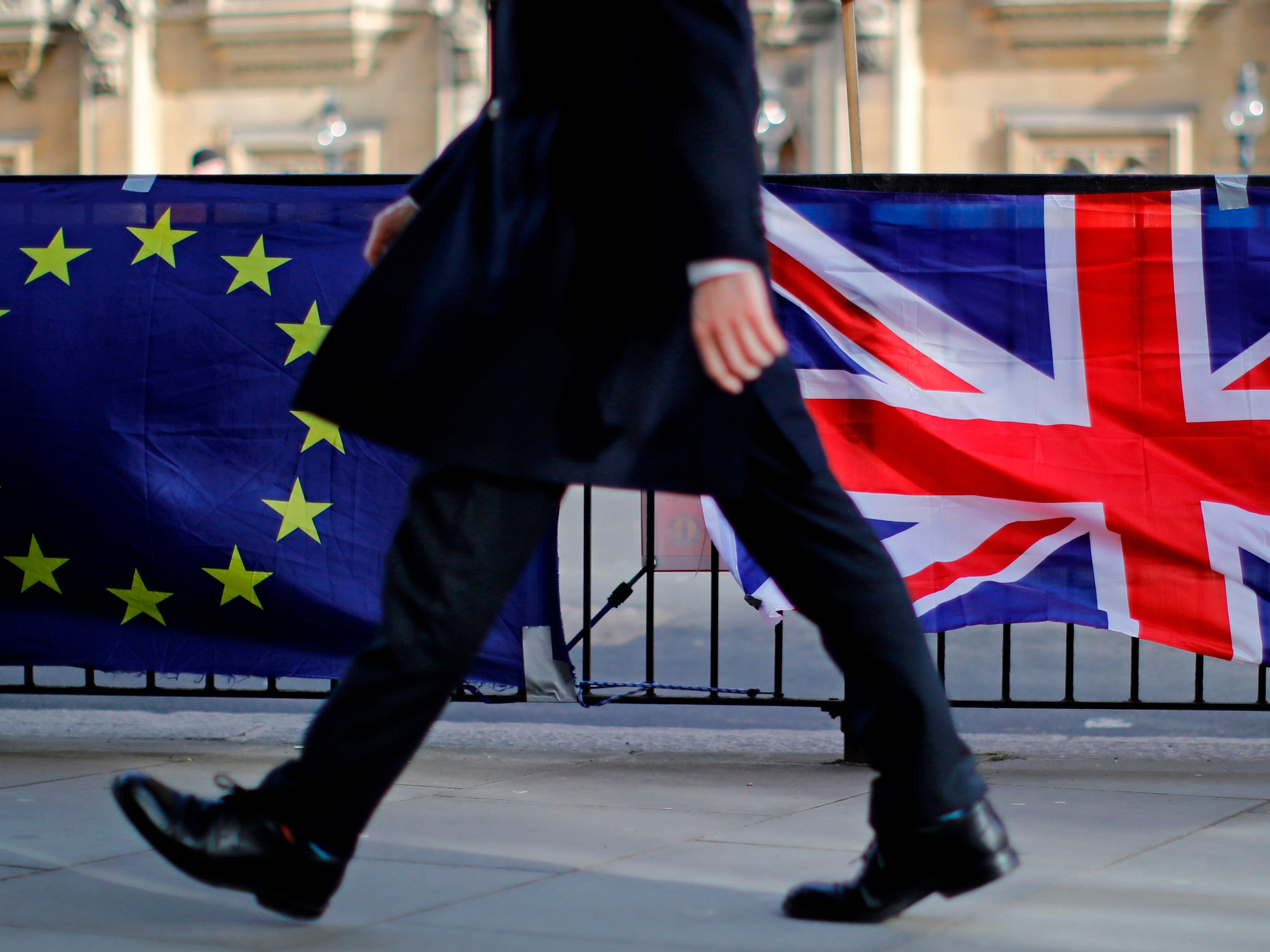 A man walks past the flags of anti-Brexit protesters outside the Houses of Parliament in London on Feb. 12, 2019. British Prime Minister Theresa May asked MPs Tuesday to give her more time for talks with the European Union on renegotiating the Brexit deal, just weeks before the scheduled March 29 departure date.
