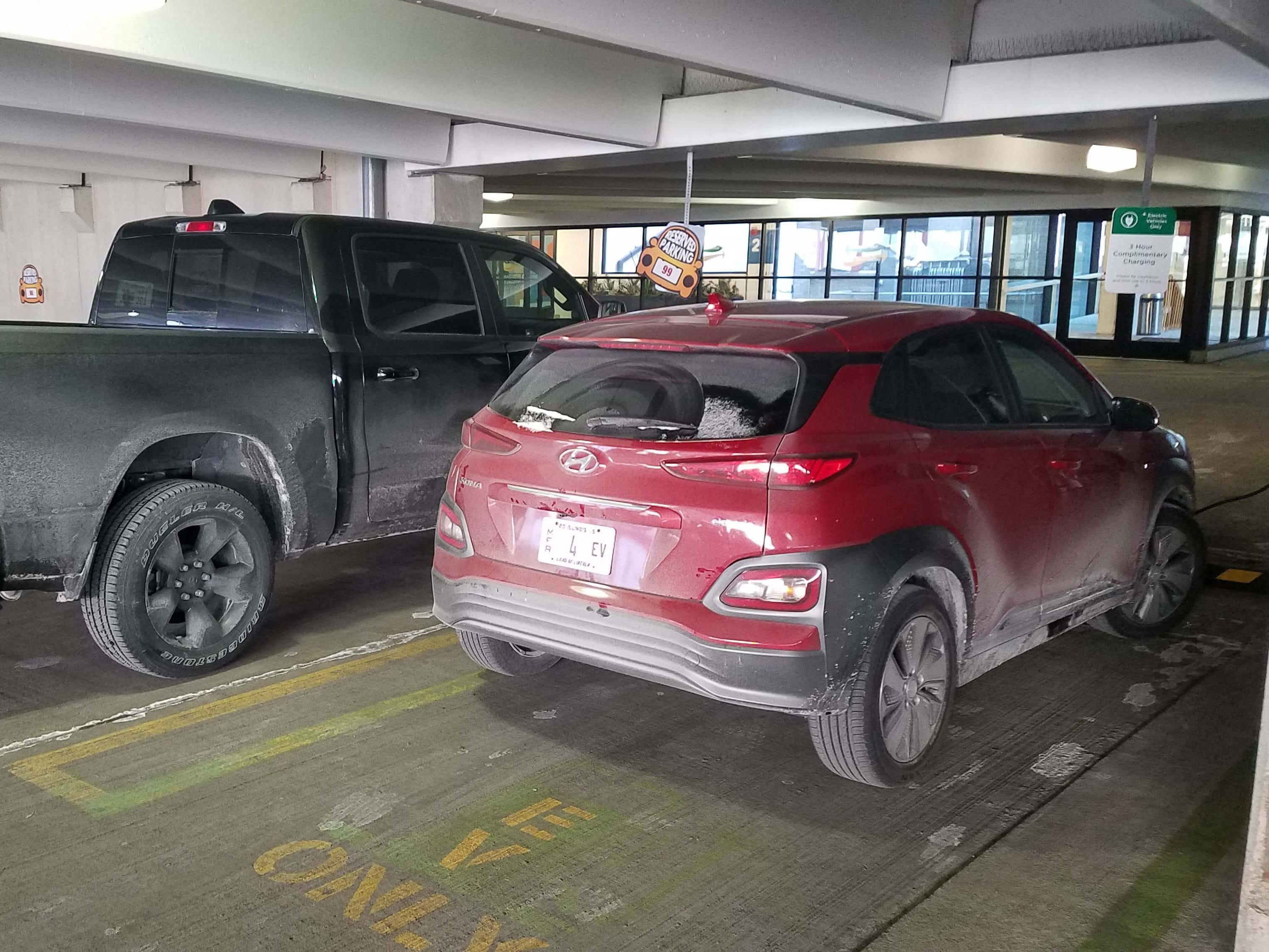 EVs only. THe 2019 Hyundai Kona EV nestles next to a pickup for warmth while it recharges in downtown Detroit.