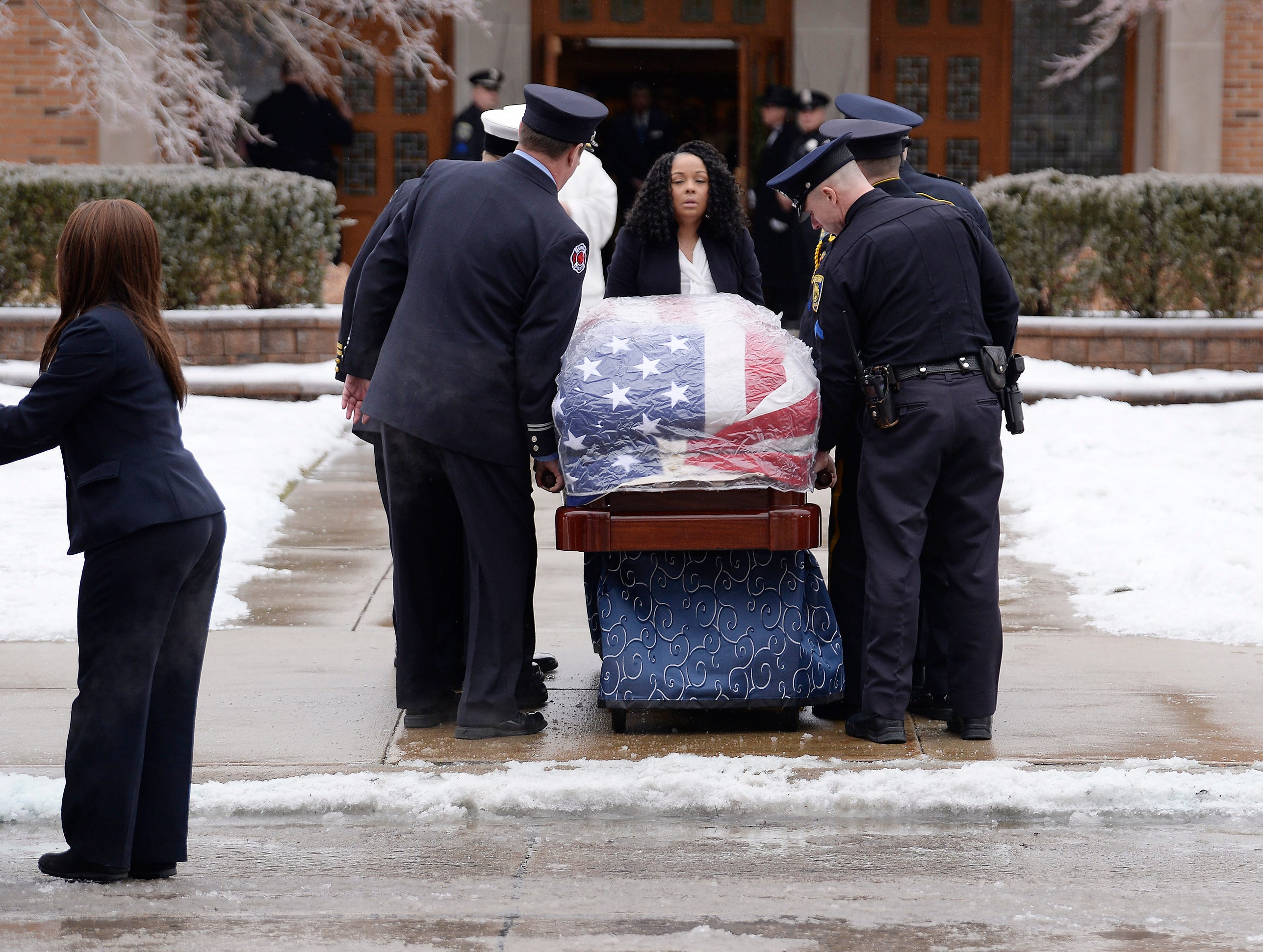 City of Dearborn first responders carry the casket of former U.S. Rep. John D. Dingell into the Church of the Divine Child for his funeral Tuesday morning.
