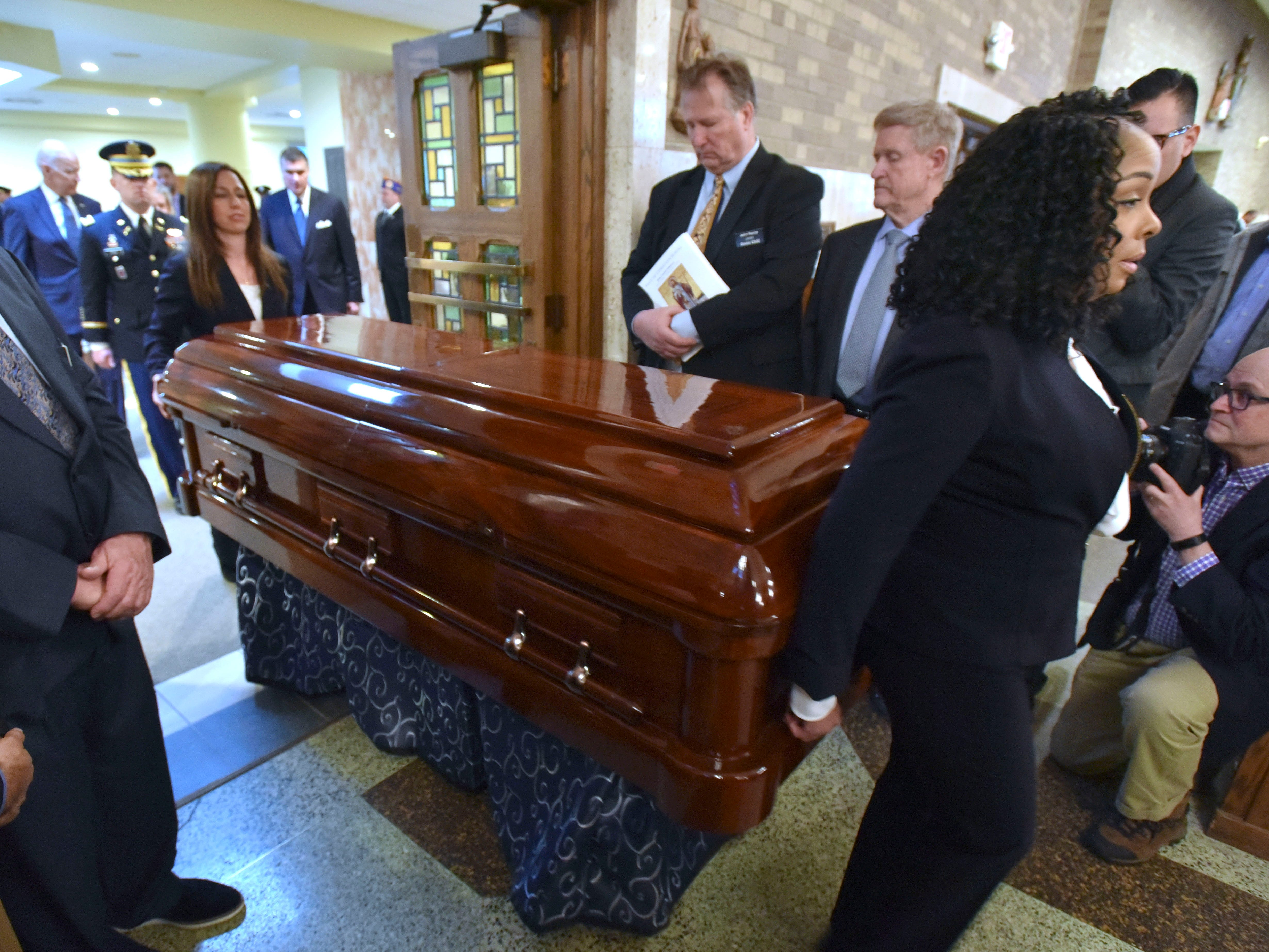 Verheyden Funeral Directors Adrianna Schnell, left, and Regina Goldsberry escort the casket of former U.S. Rep.  John Dingell into the santuary of the Church of the Divine Child in Dearborn, Tuesday.