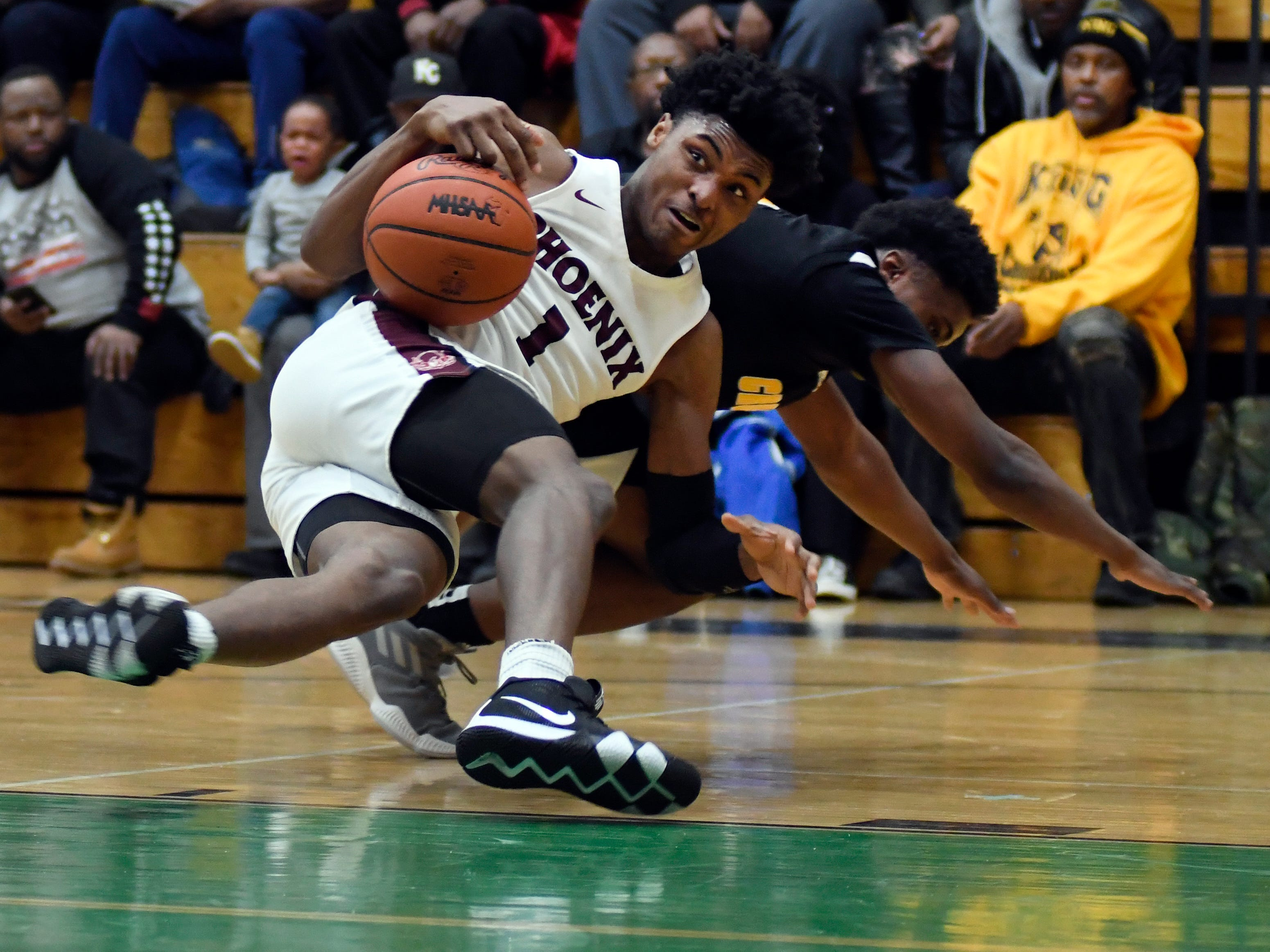 Battling for the loose ball are Detroit Renaissance's Kylin Grant (1) and Detroit King guard Jordan Whitford (3) during the second quarter.