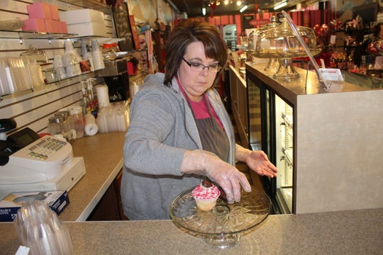 Coco Beans owner Donna McNemar prepares of a plate of cupcakes and rustic cheesecakes in preparation for Valentine's Day.