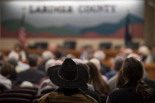 Larimer County resident Barry Feldman, center, sits midway back in the audience during a Larimer County Commissioners hearing where the commissioners voted against the current proposal for construction of the Thornton pipeline on Monday, Feb. 11, 2019, in Fort Collins, Colo.