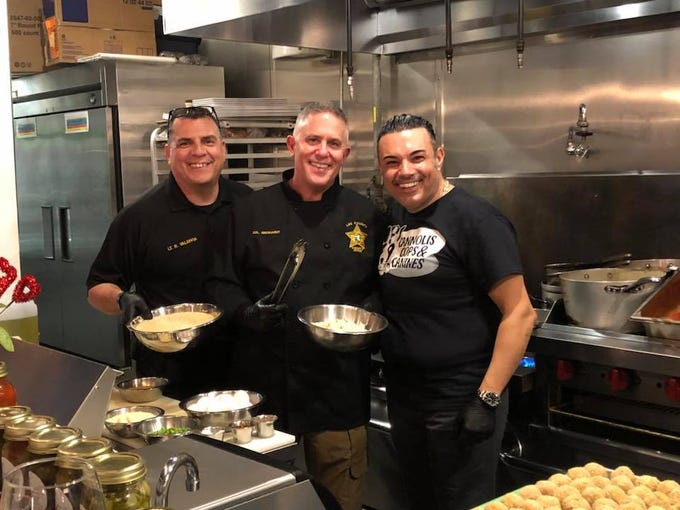 Fort Myers police Lt. Roger Valdivia and Lee County Sheriff's Office Col. Thomas Eberhardt with Cal Bruno of Bruno's of Brooklyn Italian Eatery during the  second Cannolis, Cops & Canines event hosted by Bruno's and Gulf Coast Humane Society Monday. The event raised $21,570 for the society's shelter animals.