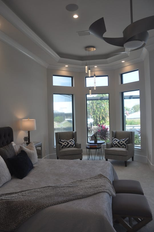 The master bedroom has windows and a sliding glass door that overlook the pool and water.