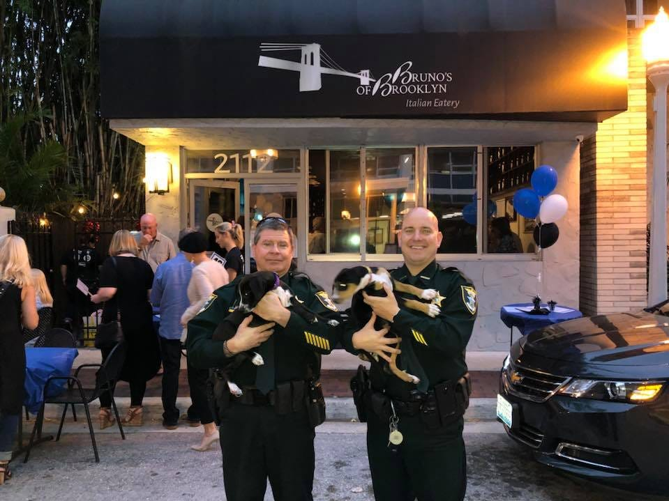 Lee County Sheriff's Office Lt.  Paul Pavese and Deputy Brett Hawkins hoist pups at the annual Cannolis, Cops & Canines event Monday sponsored by Bruno's of Brooklyn, Italian Eatery and Gulf Coast Humane Society.