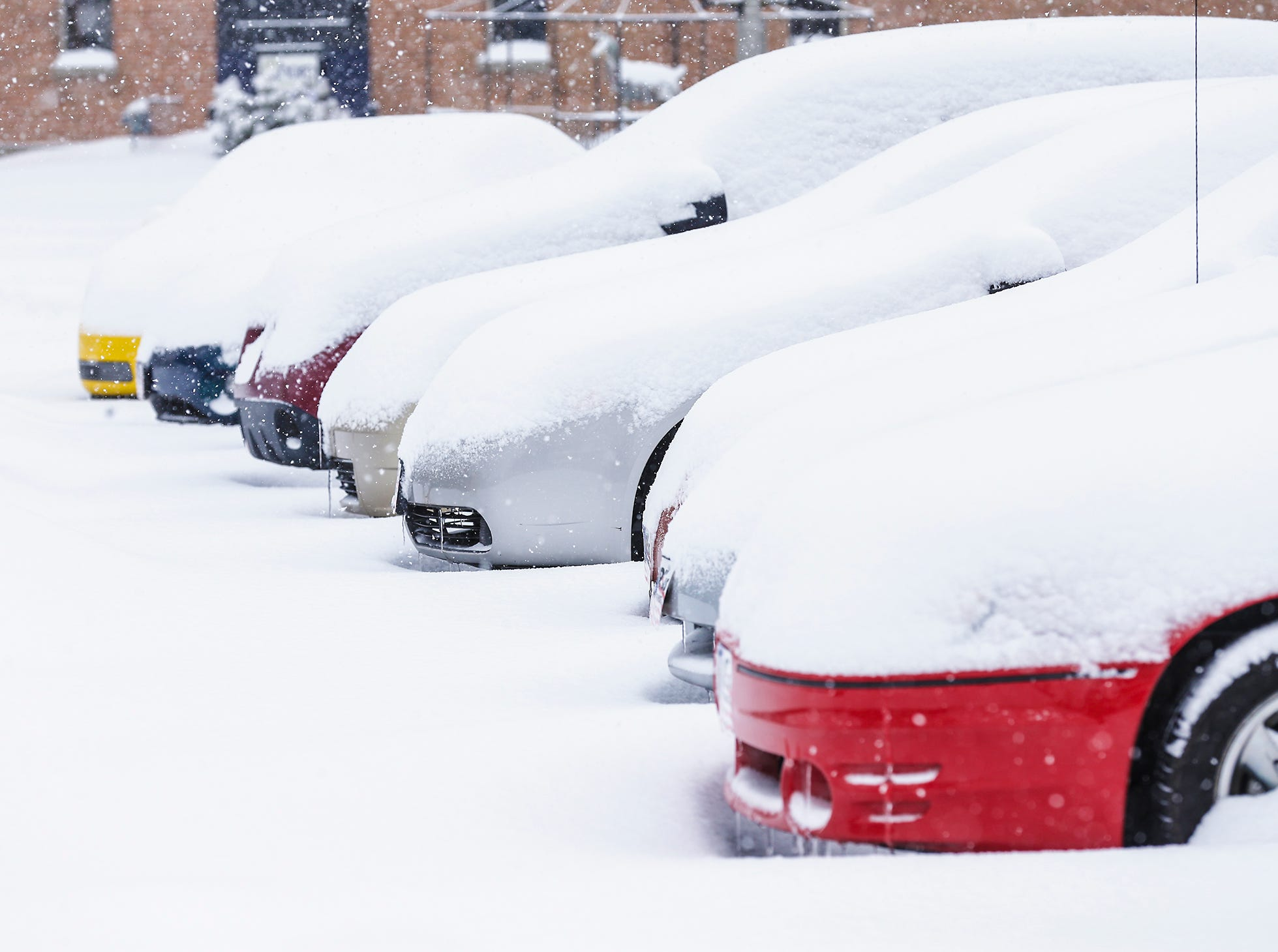 Cars for sale are covered in snow during a winter storm Tuesday, February 12, 2019 at the Cars R Us car lot on Military Road in Fond du Lac, Wis. A winter storm warning was issued for the area.