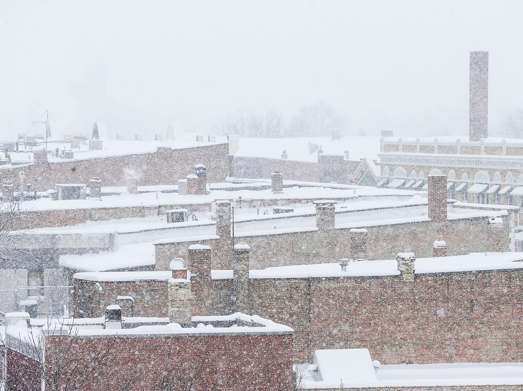 Heavy snow blankets thr rooftops of buildings during a winter storm Tuesday, Feb. 12, 2019, on Main Street in Fond du Lac, Wis. A winter storm warning was issued for the area.