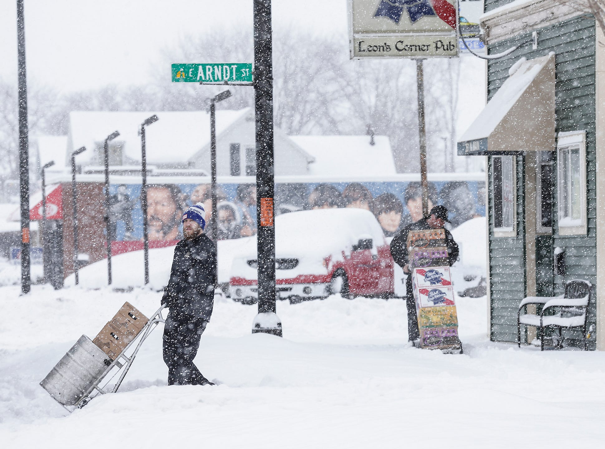 Travis Rasor and Sam Cruz of Lee Beverage deliver an order of beer during a winter storm Tuesday, February 12, 2019 to Leons Corner Pub on south north Main Street in Fond du Lac, Wis. A winter storm warning was issued for the area.