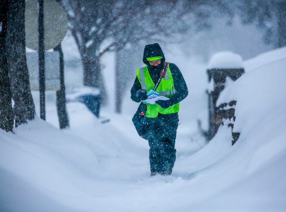 A U.S. Postal Service carrier delivers mail along First Avenue during a snowstorm Tuesday, Feb. 12, 2019, in Wausau, Wis.