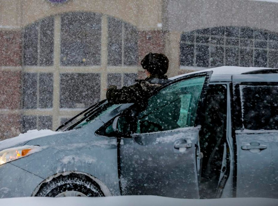 A driver cleans her windshield in the middle of Stewart Avenue during a snowstorm Tuesday, Feb. 12, 2019, in Wausau, Wis.