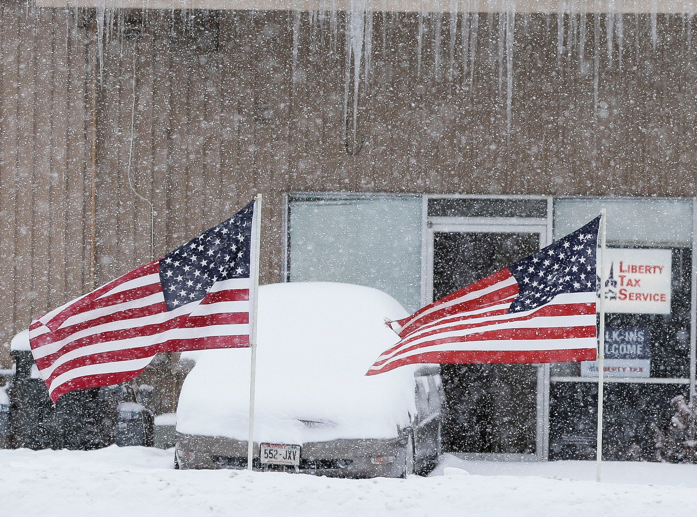 American flags flap in the wind as snow falls on Tuesday, Feb. 12, 2019, along Post Road in Stevens Point, Wis. A winter storm is expected to drop 8-11 inches of snow in central Wisconsin before clearing Tuesday night.