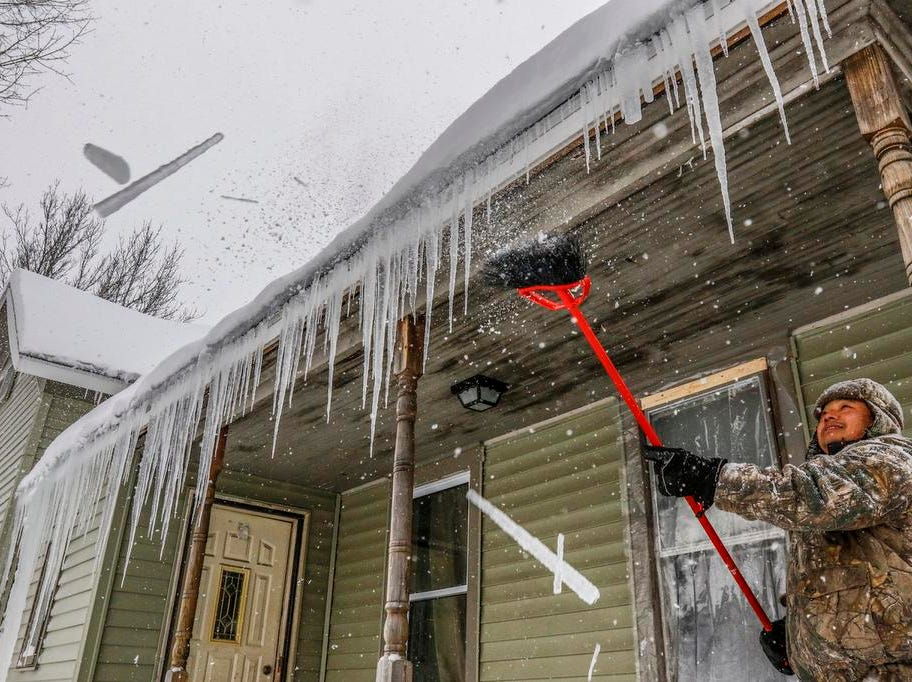 Ha Thao of Wausau chips off frozen spikes on top of his front porch during a snowstorm Tuesday, Feb. 12, 2019, in Wausau, Wis.