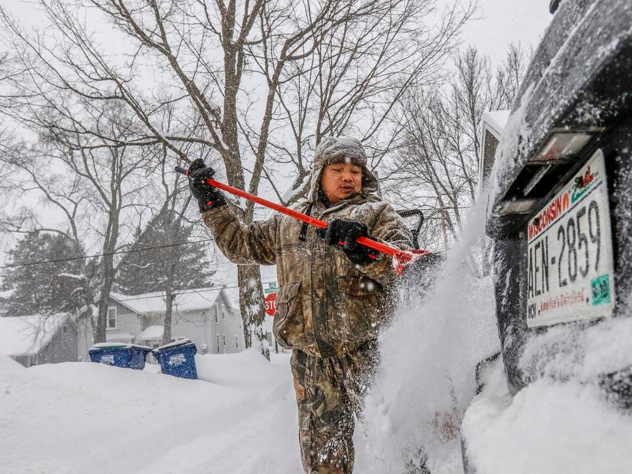 Ha Thao of Wausau uses a broom to brush snow of his vehicle during a snowstorm Tuesday, Feb. 12, 2019, in Wausau, Wis.