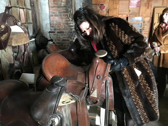 Lynn Kenyon checks out a saddle that dates from the days of the Montana Territory. Antique saddles will be among the offerings at the Forge, a new store coming to Augusta.