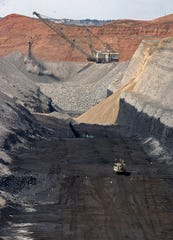 This April 4, 2013 file photo shows an 80-foot coal seam at Cloud Peak Energy's Spring Creek mine near Decker, Mont. A federal judge says mining should continue while the government reconsiders the climate impacts of a mine expansion.