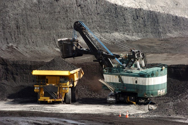 In this April 4, 2013, file photo, a mechanized shovel loads a haul truck with coal at the Spring Creek coal mine near Decker, Mont. A judge says U.S. officials should reconsider the climate change effects of expanding the mine.