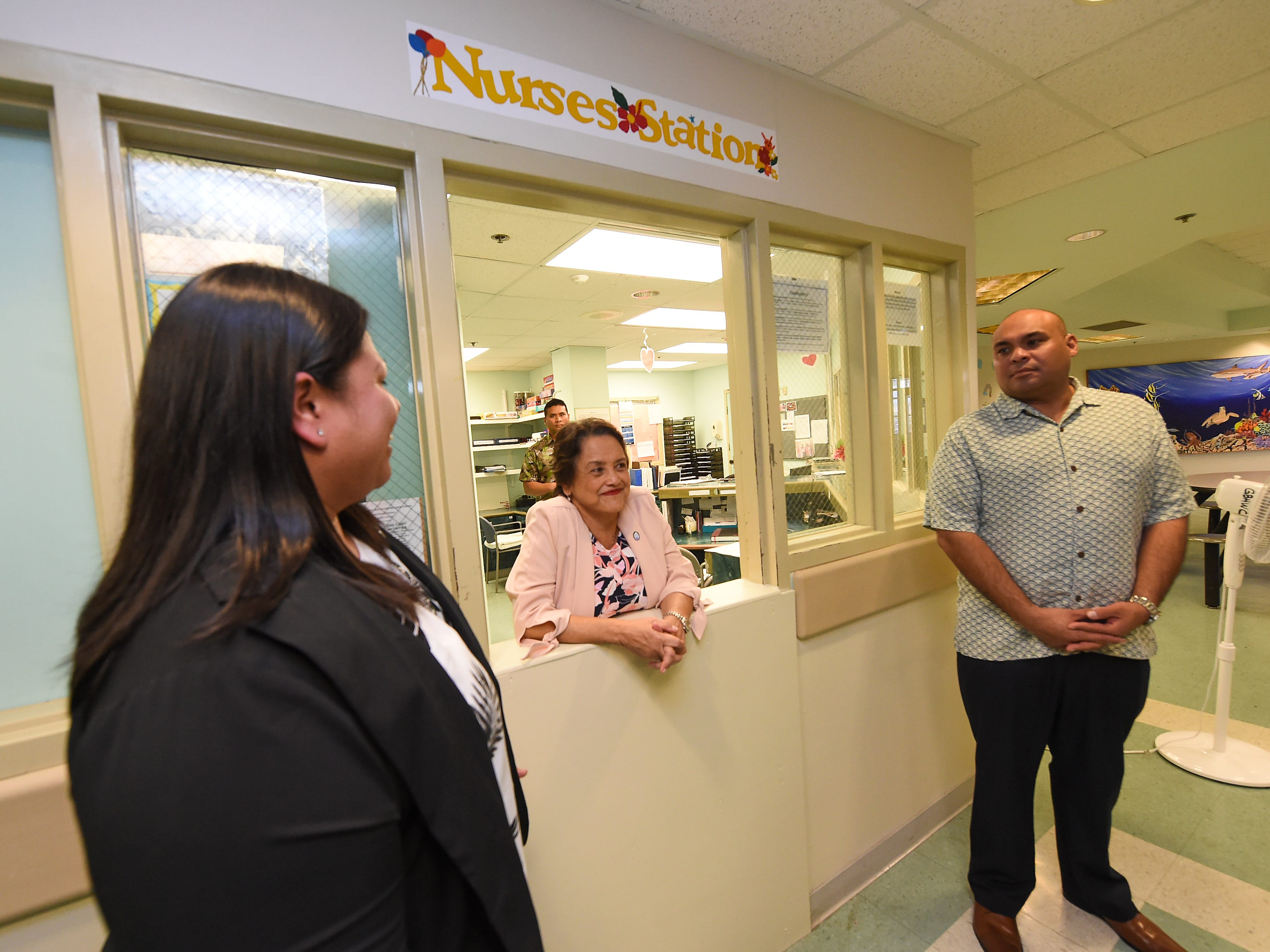 Gov. Lou Leon Guerrero, center, Carissa Pangelinan, deputy director of the Guam Behavioral Health and Wellness Center, and Lt. Gov. Josh Tenorio, stand at the facility's nurses station during a tour on Feb. 12, 2019.