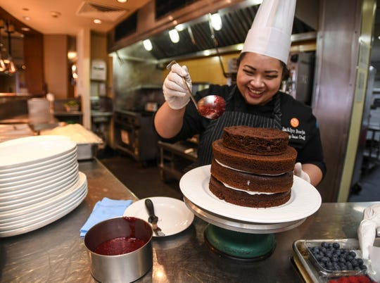 Working on the fourth of six layers, Pacific Islands Club Pastry Sous Chef Jacklyn Borja, shares some of her humor as she builds a naked berry cake at the hotel's Bistro restaurant in Tumon on Feb. 7, 2019.