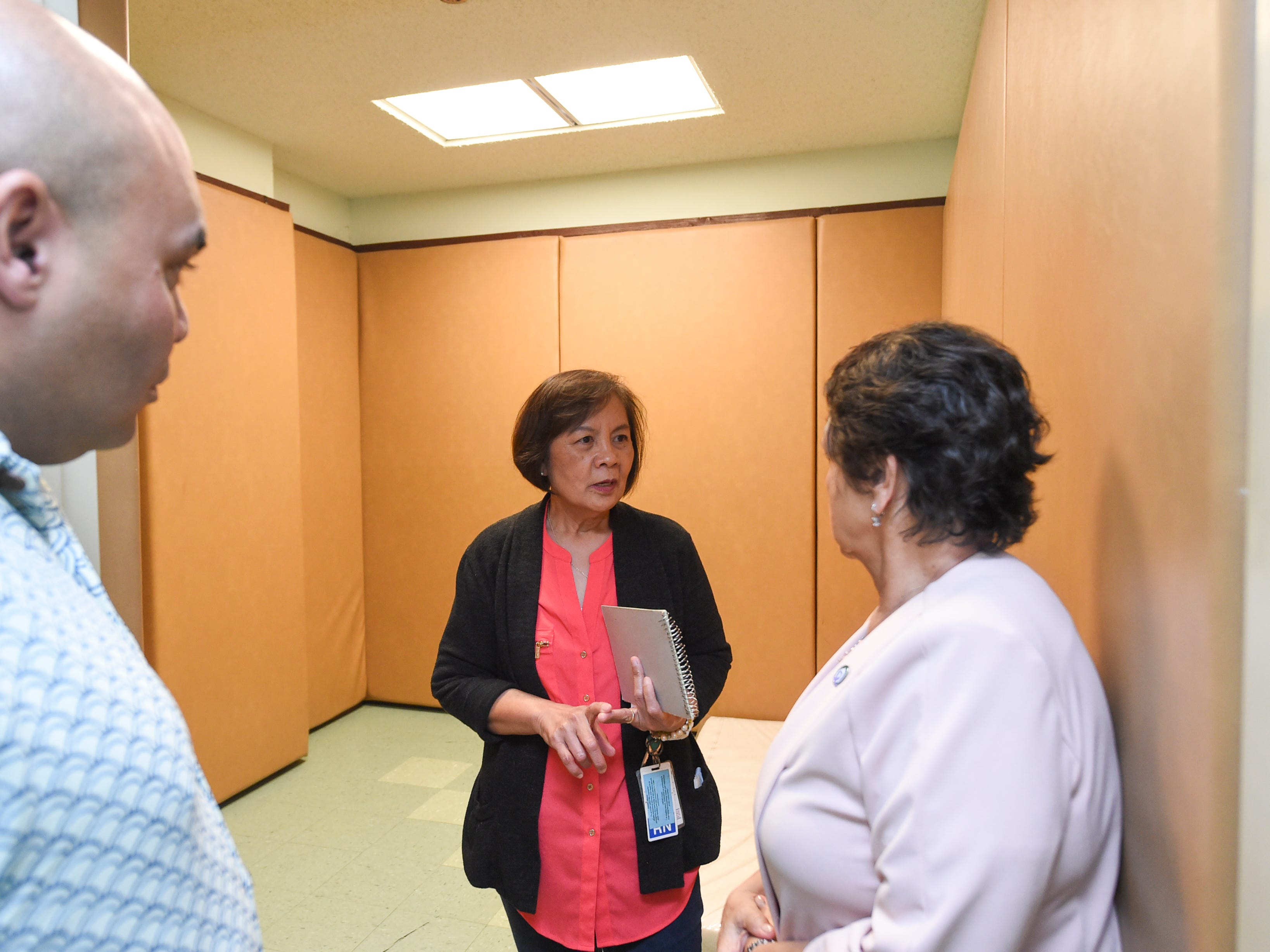 Rosemin M. Sogo-an, a Guam Behavioral Health and Wellness Center psychiatric nurse, center, speaks with Gov. Lou Leon Guerrero and Lt. Gov. Josh Tenorio inside of a padded cell during a tour of their Tamuning facility on Feb. 12, 2019.