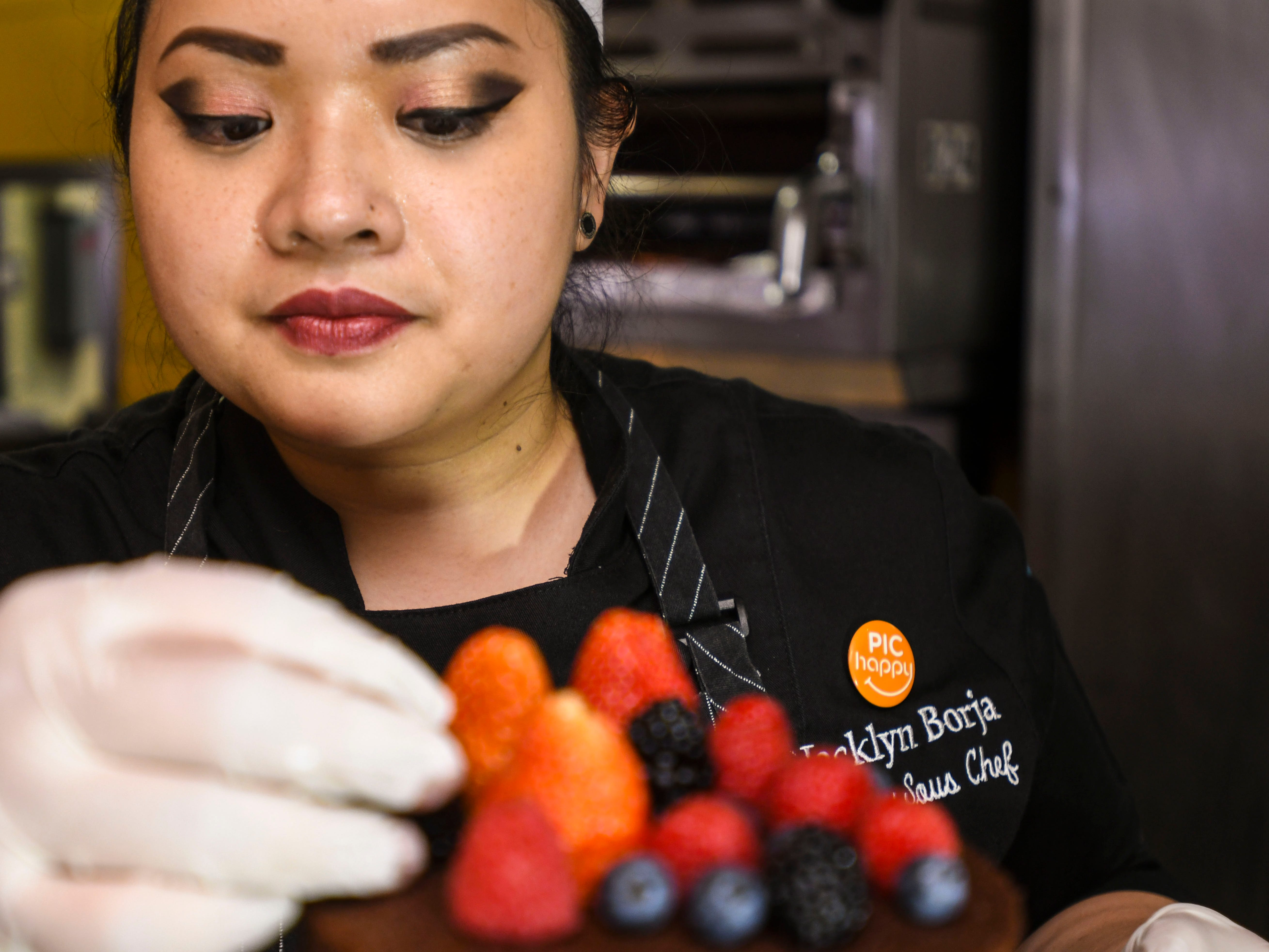 Jacklyn Borja, Pacific Islands Club pastry sous chef, meticulously arranges an assortment of fresh berries to top off a naked berry cake at the hotel's Bistro restaurant in Tumon on Feb. 7, 2019.