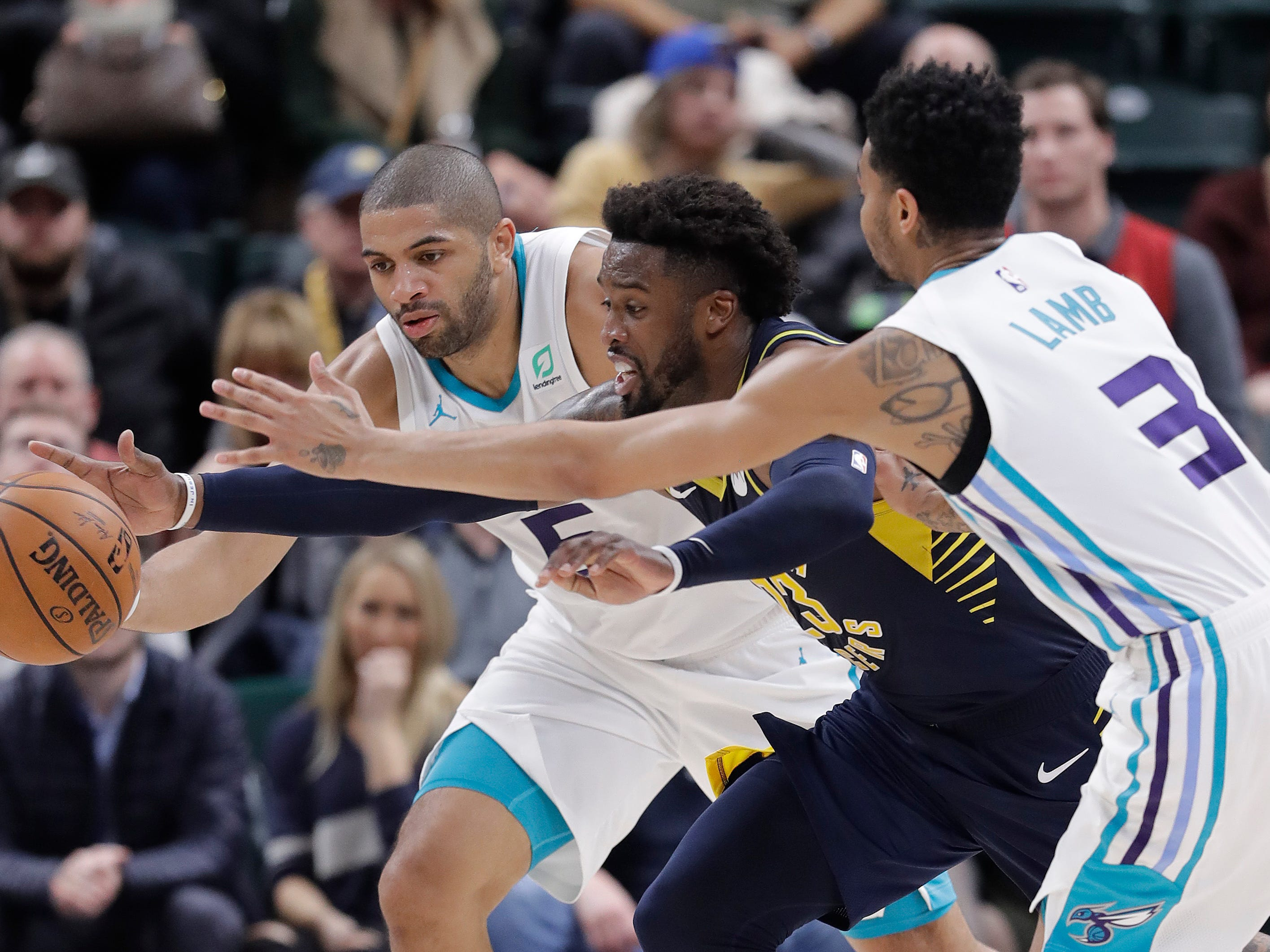 Indiana Pacers' Wesley Matthews, center, goes for a loose ball against Charlotte Hornets' Nicolas Batum, left, and Jeremy Lamb, right, during the second half of an NBA basketball game, Monday, Feb. 11, 2019, in Indianapolis. Indiana won 99-90.