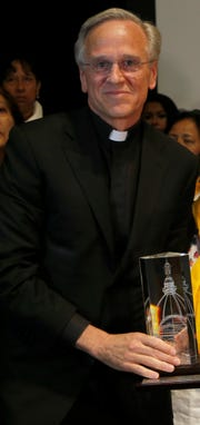 "Reverend John I. Jenkins, rector of Notre Dame University, presents the volunteer group ""Colectivo Solecito,"" or Little Sun Collective, with an award in Mexico City, Tuesday, Oct. 16, 2018. The University of Notre Dame has presented its 2018 Notre Dame Award to the group of Mexican mothers who have led a tireless, years-long search for missing loved ones in Mexico's Gulf coast state of Veracruz. (AP Photo/Marco Ugarte)"