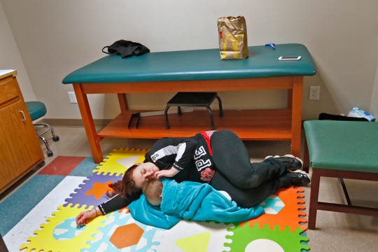 Jeremiah Cox rests with him mother, Ashley Cox, at Hanger Clinic.