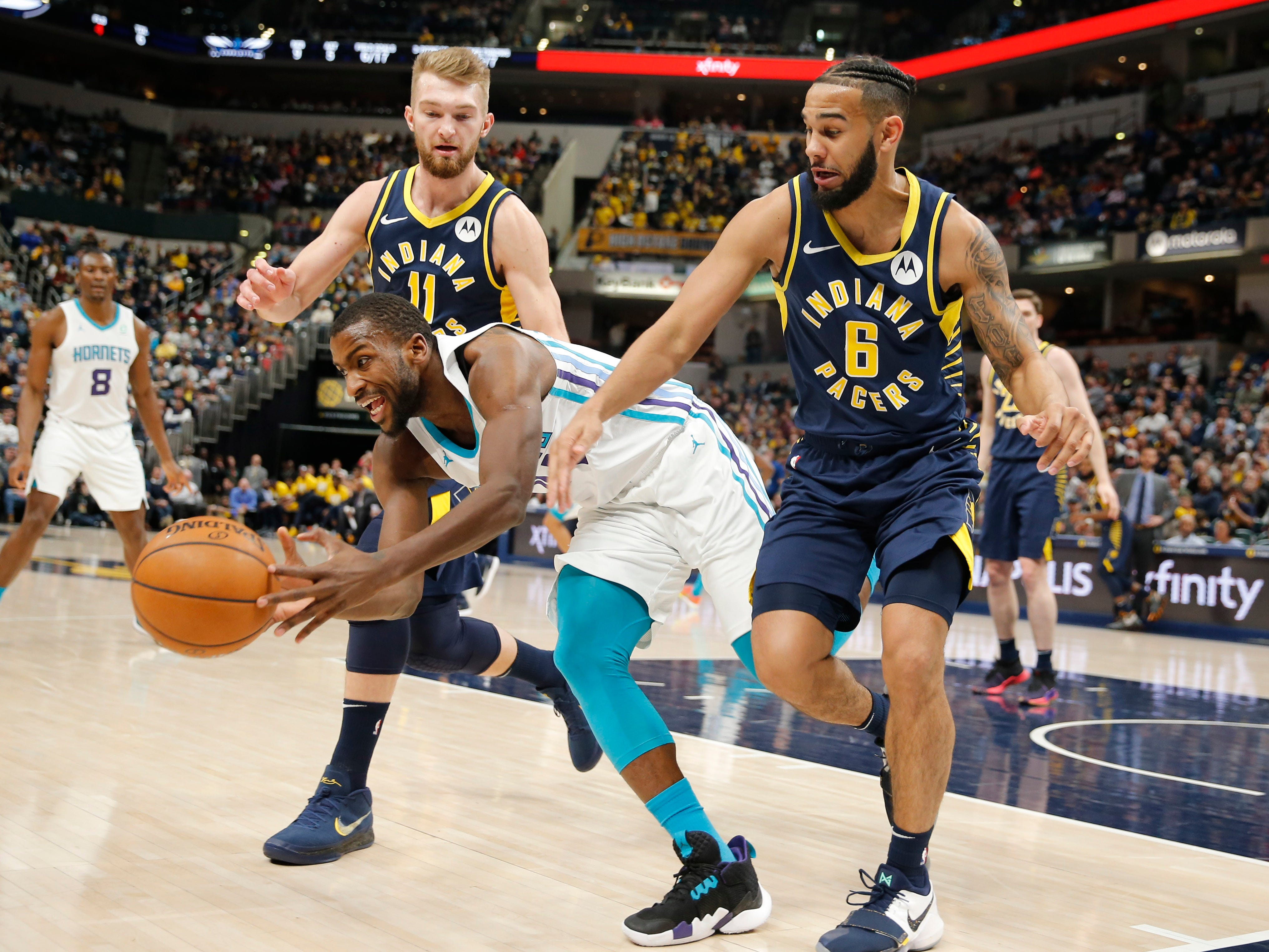 Feb 11, 2019; Indianapolis, IN, USA; Charlotte Hornets forward Michael Kidd-Gilchrist (14) chases after a loose ball against Indiana Pacers guard Cory Joseph (6) and forward Domantas Sabonis (11) during the first quarter at Bankers Life Fieldhouse.