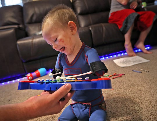 Jeremiah Cox plays an instrument during occupational therapy at his home.